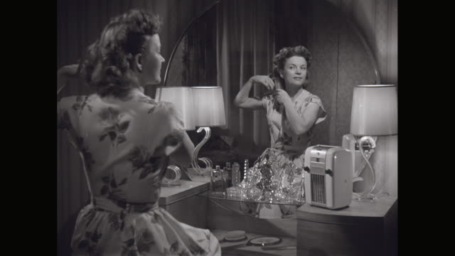 ms woman looking into mirror combing her hair and listening radio in domestic room / united states - radio video stock e b–roll