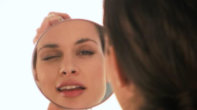 vídeos de stock, filmes e b-roll de hd: mulher olhando para um espelho - batom