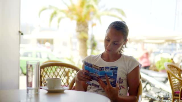 woman looking leaflet at cafe - flyer leaflet stock videos and b-roll footage