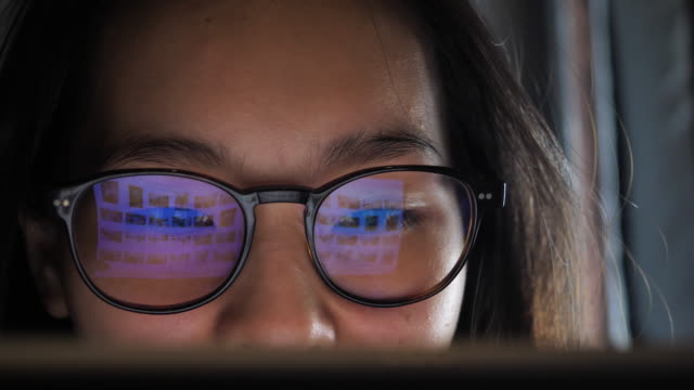 woman looking on computer, refection on eye glasses - occhiali da vista video stock e b–roll
