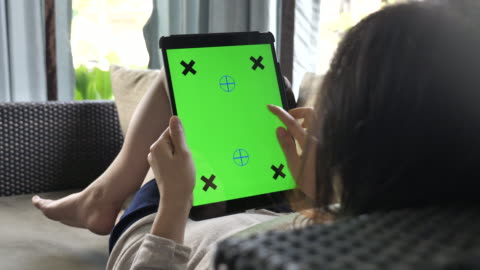 stockvideo's en b-roll-footage met vrouw op zoek op digitale tablet met green screen op de sofa thuis, verticaal - over shoulder