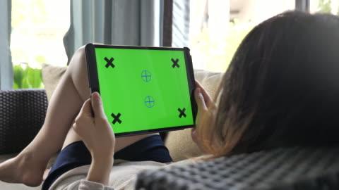 stockvideo's en b-roll-footage met vrouw op zoek op digitale tablet met green screen op de sofa thuis, horizontaal - over shoulder