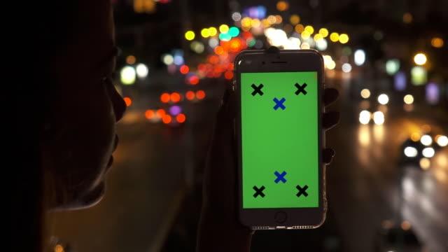 vídeos de stock, filmes e b-roll de mulher procurando telefone de tela verde com bokeh da luz - send