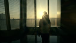 Woman looking out in office with sunset