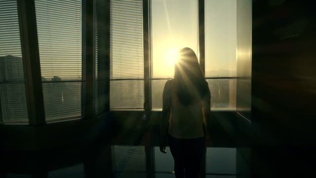 vídeos de stock e filmes b-roll de woman looking out in office with sunset - autoconfiança