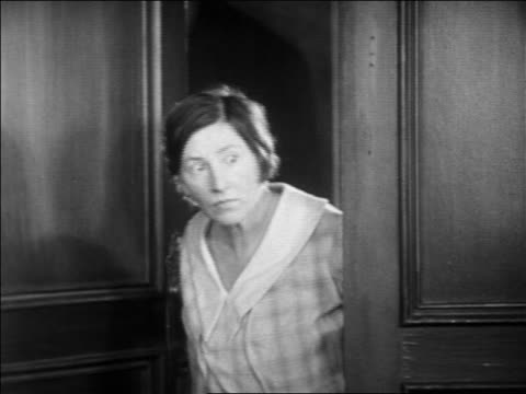 b/w 1931 woman looking out of door with shocked expression + starting to shut door / feature - 1931 stock videos & royalty-free footage