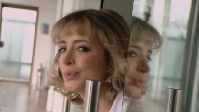 cu woman looking out of glass doors in empty office, giving a sly smile to the camera, and closing doors/ london, england - empty glass stock videos and b-roll footage