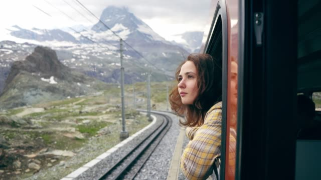 woman looking out of the window on the train near matterhorn - treno video stock e b–roll