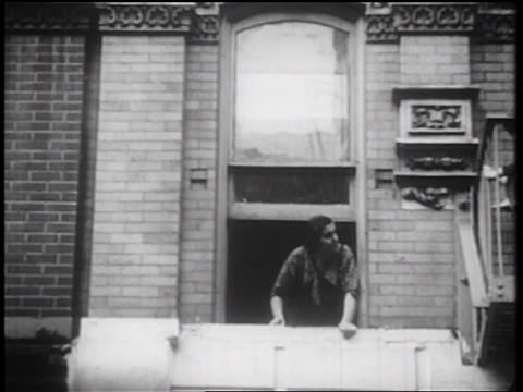 b/w 1939 woman looking out of window / nyc / documentary - fensterfront stock-videos und b-roll-filmmaterial