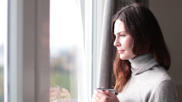 Woman looking out of window with morning coffee