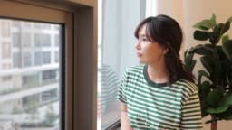 woman looking out the window from home