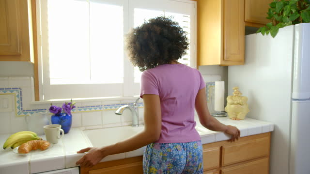 woman looking out window in kitchen - curly stock videos & royalty-free footage