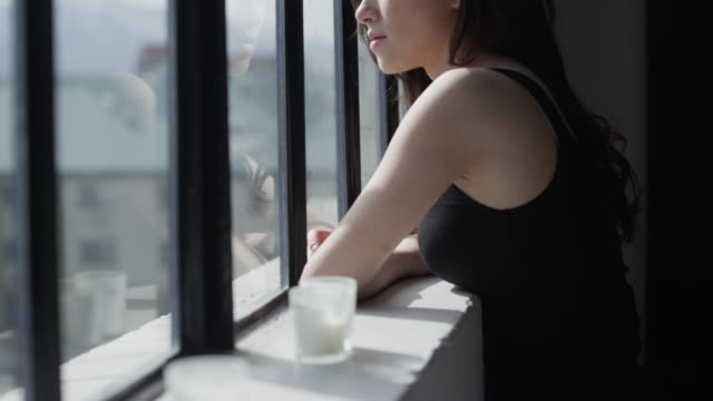 slo mo ms tu woman looking out window / salt lake city, utah, usa - aspettare video stock e b–roll