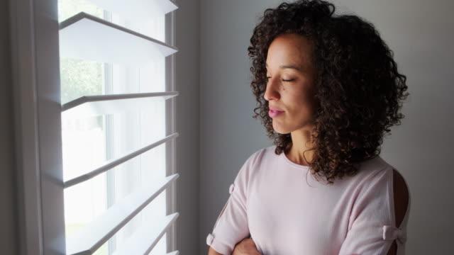 vídeos de stock, filmes e b-roll de mulher olhando para fora da janela - só uma mulher jovem