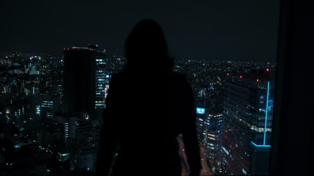 woman looking over the city of tokyo, japan at night - blick durchs fenster stock-videos und b-roll-filmmaterial