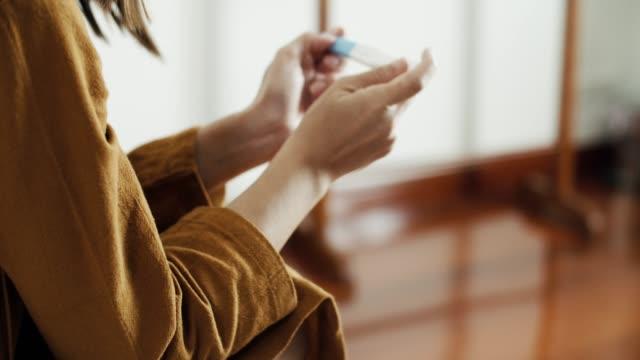 kit di test di gravidanza dall'aspetto femminile positivo - ovulazione video stock e b–roll