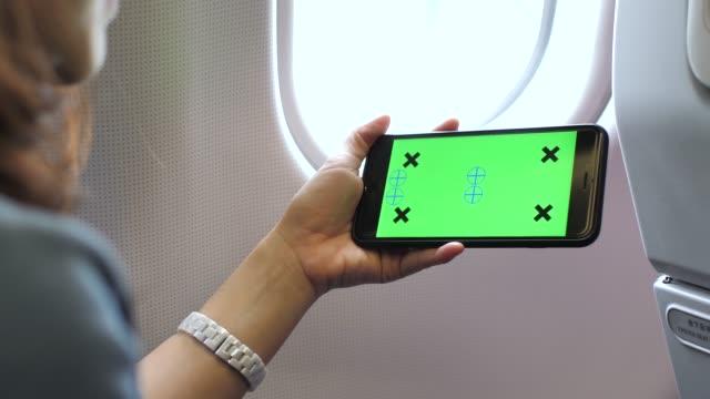 vídeos de stock, filmes e b-roll de telefone inteligente de mulher olhando com chroma key em avião, horizontal - horizontal