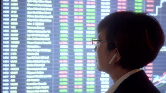 vídeos de stock, filmes e b-roll de mulher olhando mercado de ações dados em tela grande - ponto turístico