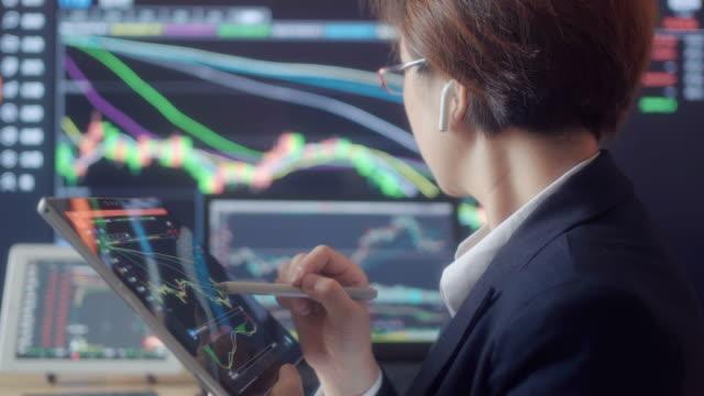 vidéos et rushes de femme regardant des données de marché boursier sur l'écran - marché boursier