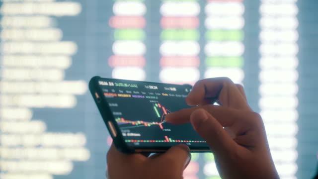 vídeos de stock, filmes e b-roll de mulher olhando mercado de ações dados no telefone inteligente - casa de câmbio