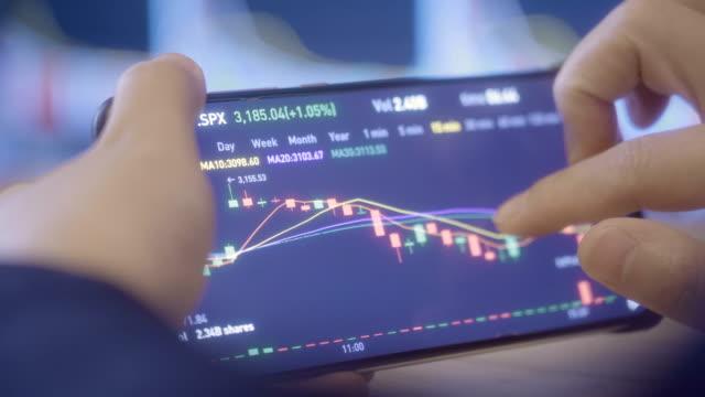 スマートフォンで株式市場データを探している女性 - 操作する点の映像素材/bロール