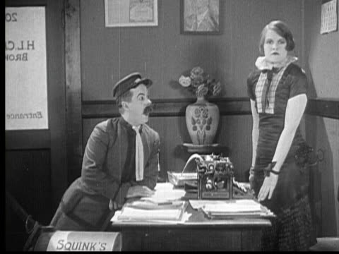stockvideo's en b-roll-footage met 1924 b/w montage cu woman (natalie kingston) looking surprised / ms woman standing up and punching man (billy bevan) in his face / cu man holding his face in pain / usa - slaan met vuist