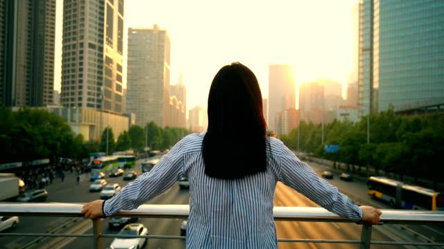 vidéos et rushes de woman looking the beautiful city sunset - derrière