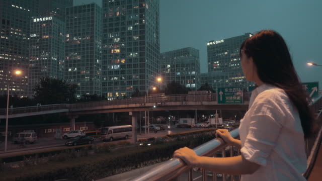 Woman looking the city at night
