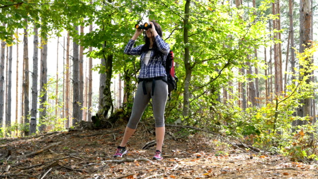 Woman looking through binoculars while hiking in the mountains.