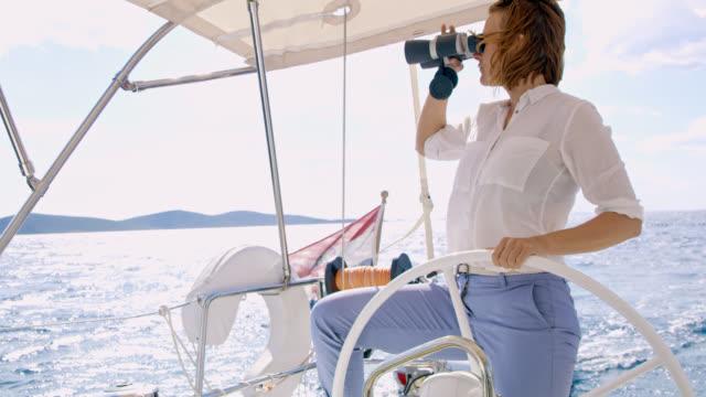 ws kvinna tittar genom kikaren när du navigerar en segelbåt - kapten bildbanksvideor och videomaterial från bakom kulisserna