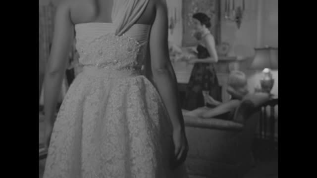 Woman looking through black lace / man running lace looms / CU white lace / lace cocktail dresses and evening gowns / model in front of piano with...
