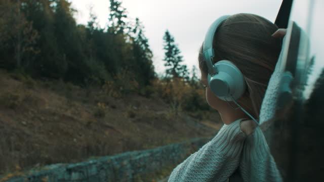 frau auf der suche durch autofenster und musik über kopfhörer hören - kopfhörer stock-videos und b-roll-filmmaterial