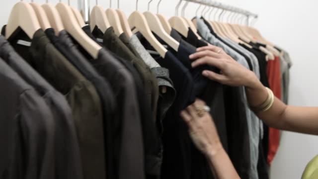 woman looking through clothes on rail in boutique - bluse stock-videos und b-roll-filmmaterial