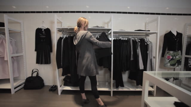 ms pan woman looking through clothing rack in fashionable clothing store / new york city, new york, usa - clothing store stock videos and b-roll footage