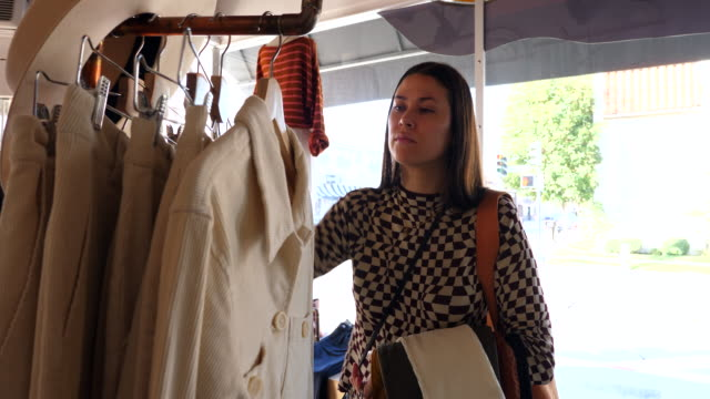 ms woman looking through clothing rack while shopping in boutique - pantaloni video stock e b–roll