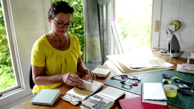 woman looking through notebook - stoffmuster stock-videos und b-roll-filmmaterial