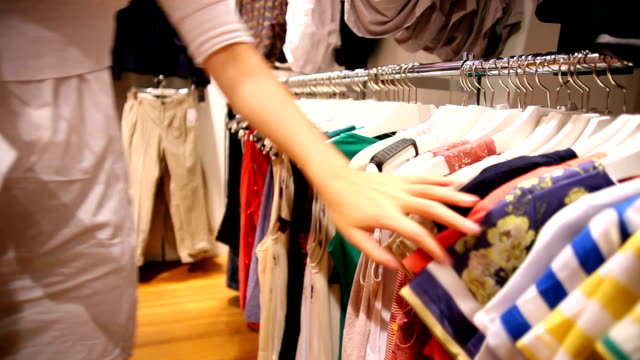 woman looking through shirts at a store - boutique stock videos & royalty-free footage