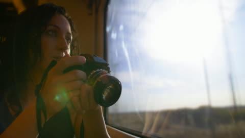 woman looking through the train window and taking pictures - digital spegelreflexkamera bildbanksvideor och videomaterial från bakom kulisserna