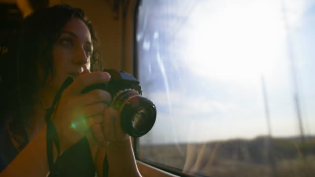 Woman looking through the train window and taking pictures