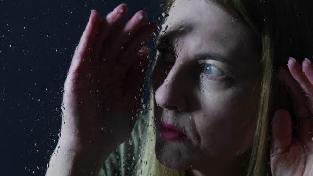 woman looking through wet window - peeking stock videos & royalty-free footage