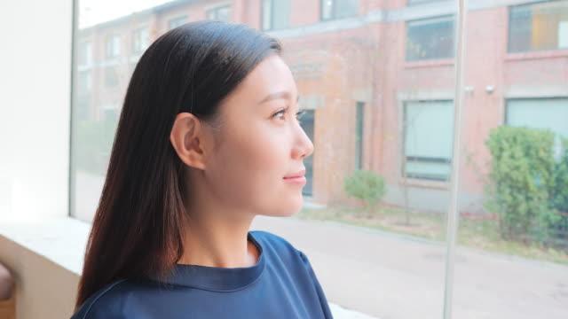 ms woman looking through window and smiling at camera - 中国人点の映像素材/bロール
