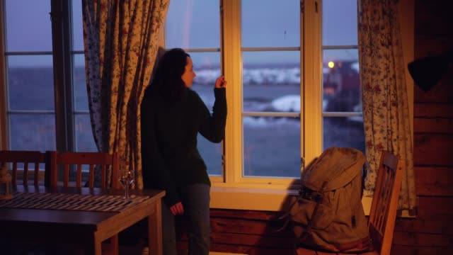 woman looking through window from cabin  on lofoten islands in winter - indoors stock videos & royalty-free footage