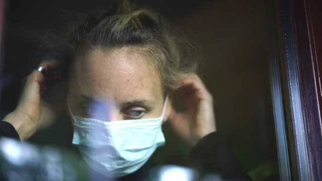 woman looking through window puts on face mask - wellbeing stock videos & royalty-free footage