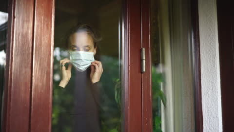 woman looking through window puts on face mask - social issues stock videos & royalty-free footage