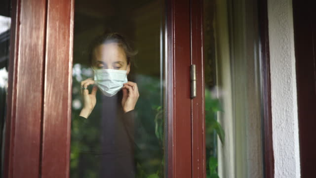 vídeos de stock e filmes b-roll de woman looking through window puts on face mask - saúde e segurança ocupacional