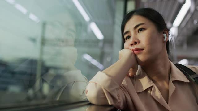 vidéos et rushes de femme regardant à travers le train de fenêtre et écoutant de la musique - transport