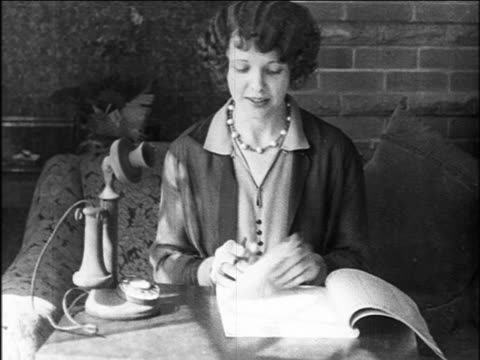 b/w 1927 woman looking thru telephone directory / newsreel - directory stock videos and b-roll footage
