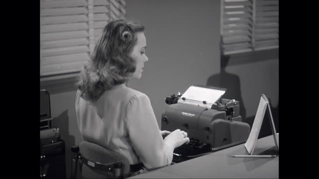 ms woman looking to notepad and typing on antique typewriter in office / united states - 以前の点の映像素材/bロール