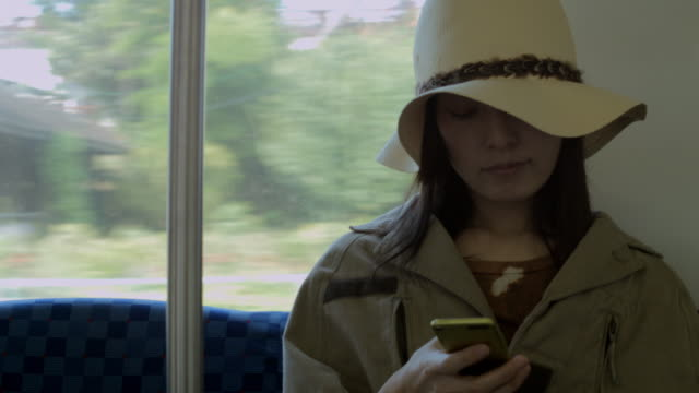 CU Woman looking to smartphone on train / Nerima, Tokyo, Japan