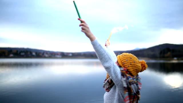 vidéos et rushes de femme à la recherche du lac, tenant des étincelles - châle